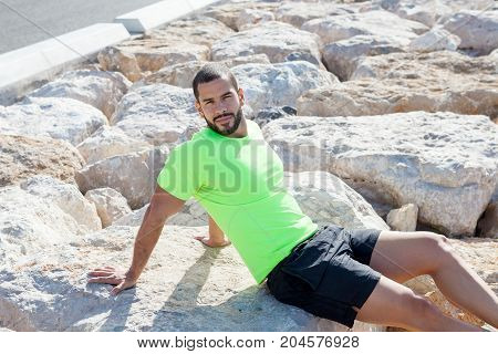 Serious young handsome strong man looking at camera, relaxing and sitting on stones on sea shore