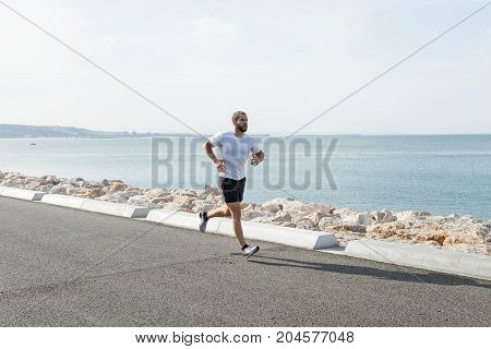 Serious young muscular man wearing sportswear and running on seaside road with sea in background