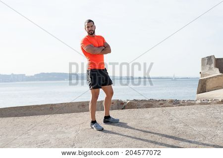 Portrait of serious young handsome strong man wearing sportswear, looking at camera and standing with his arms crossed and river in background