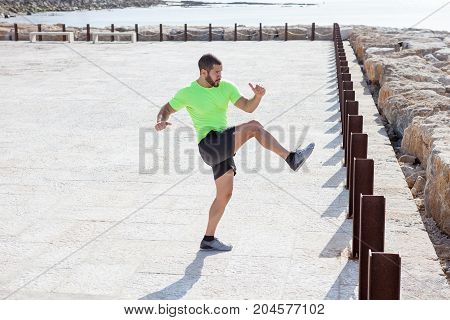 Young serious strong handsome man wearing sportswear and doing leg swings outdoors