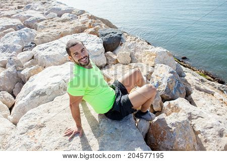 Portrait of young handsome sporty man looking at camera and sitting on stones on sea shore. High angle view.