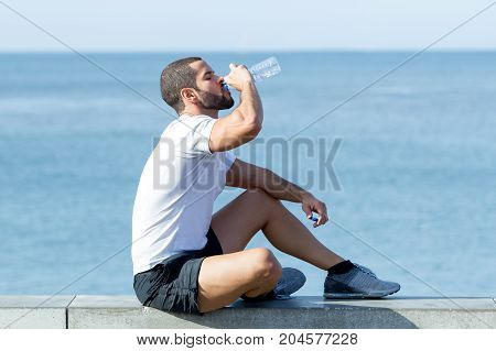 Portrait of young handsome strong man wearing sportswear, drinking water from bottle and sitting on parapet. Side view.