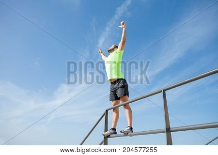 Cheerful young muscular man wearing sportswear, pumping fists, raising arms and standing on railing. Low angle view.