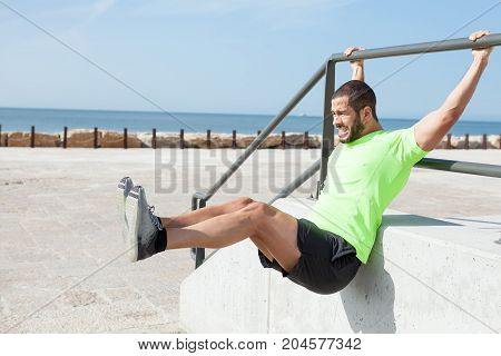 Portrait of tensed young strong handsome man wearing sportswear, hanging on stair railing and doing leg raises at seaside