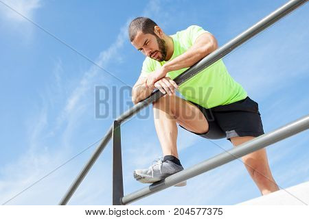 Portrait of young handsome strong man wearing sportswear, looking downwards, relaxing and leaning on railing. Low angle view.