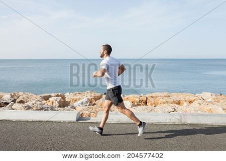Serious young strong man wearing sportswear and running on seaside road with sea in background. Side view.