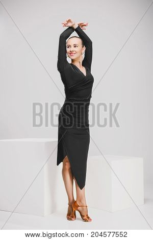 elegant girl in black dress posing in studio, woman showing one movement from dance