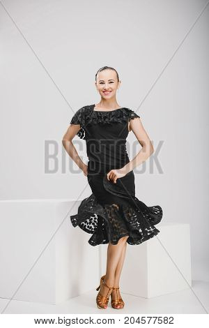 pretty girl in a black dress dancing in a white studio, young woman smiling and posing in front of camera