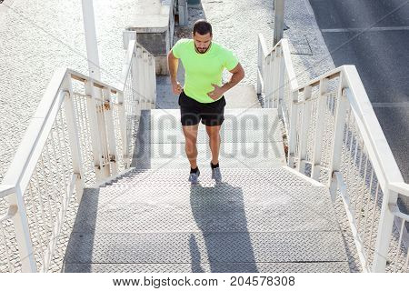 Concentrated male athlete running up stairs to make training more intensive. Sporty handsome young man training alone outdoors. Staircase workout concept