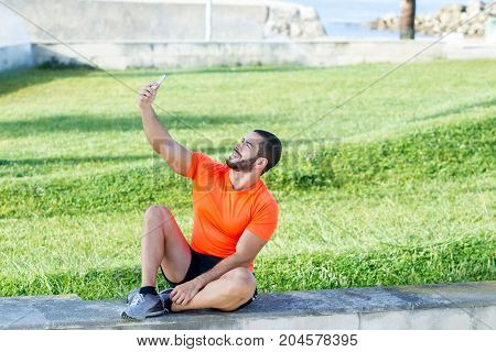 Content strong man making selfie outdoors after training. Happy brutal young athlete enjoying summer weather and modern life. He sitting on concrete slab and photographing himself. Social media concept