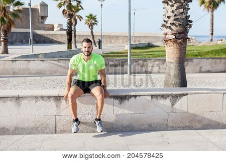 Handsome male athlete relaxing after training and sitting on concrete slab. Confident young man in sport clothing looking at camera and resting outdoors. Sportsman concept