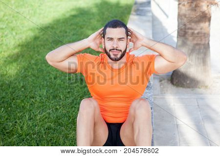 Sporty brutal young man doing stomach crunches and looking at camera outdoors, Serious handsome male athlete with hands behind head exercising in park. Morning training concept