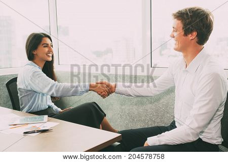 Cheerful business partners shaking hands in meeting room to congratulate each other with successful deal. Positive executives counting on continued collaboration. Bargain concept
