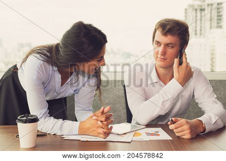 Cheerful Indian secretary helping boss with paperwork. Busy male executive talking on phone and making notes during staff meeting with colleague. They planning new deal. Cooperation concept