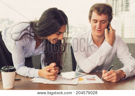 Confident male colleague negotiating on phone and recording important information. Smiling Indian woman reading message on paper. Handsome manager making notes for coworker. Business lifestyle concept