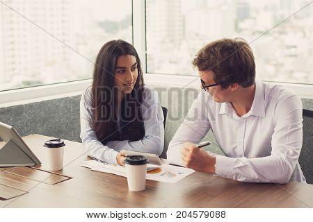 Interracial business partners discussing deal during meeting in board room. Confident Indian businesswoman showing information on smartphone to colleague as proof. Teamwork concept
