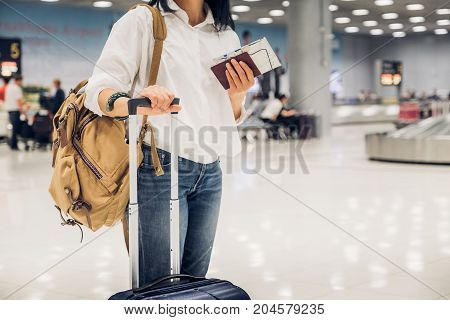 Woman Backpacker Holding Passport And Map With Suitcase Standing At Check In Baggage At Airport Term