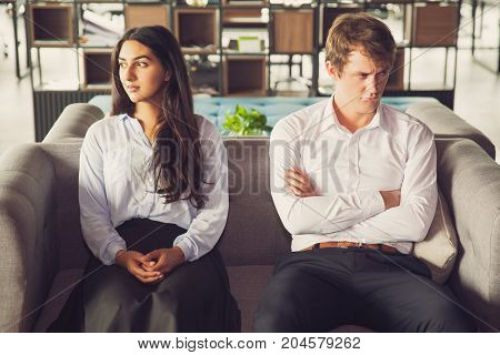 Resentful colleagues looking away from each other because of misunderstanding. Unhappy business people being quarreling and sitting on one sofa. Conflict concept