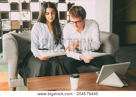 Sophisticated colleagues examining papers and discussing mistakes in office. Smart male manager pointing at document and explaining information to colleague. Discussion concept