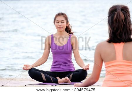Yoga class at sea beach Master guru doing lotus pose with clam relax emotion in front of student Meditation poseWellness and Healthy balance lifestyle.