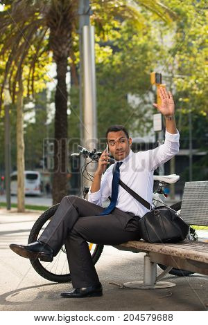 Young Hispanic businessman sitting on bench in park, talking on smartphone, bike nearby. Male office worker waving to his colleague