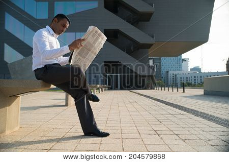 Concentrated Hispanic businessman sitting outdoors and reading newspaper. Young male office worker studying paper with financial report. Business news concept