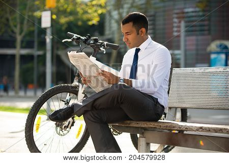 Concentrated Hispanic executive manager sitting on bench and reading newspaper during lunchtime, bike nearby. Young male office worker studying financial report. Business news concept