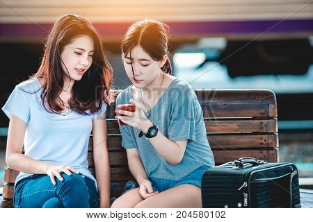 Teen Asian girls use smart-phone for checked baggage train platform area prepared to ready to go outside. Thailand on weekends. From Bangkok to Chiang Mai