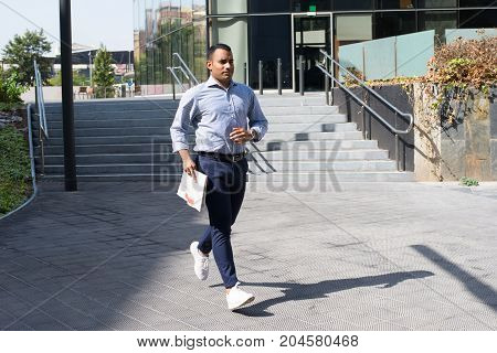 Hispanic young man wearing striped shirt and navy pants, holding newspaper and running in street. Businessman running late to meeting with friend. Lifestyle concept