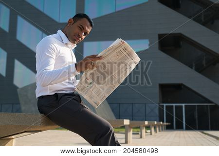 Handsome Latin businessman sitting outside office and reading newspaper. Young male office worker with newspaper looking at camera. Business news concept