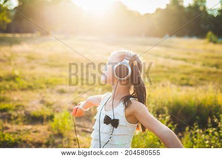 Joyful girl listening music with headphones and dancing, haappy child listening music