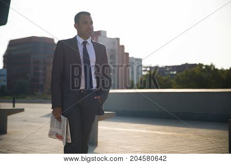 Pensive young businessman wearing suit and tie, holding newspaper, walking on street and looking aside. Confident male executive thinking about recent news. Business news concept