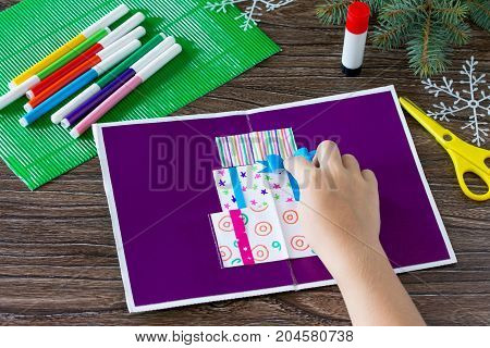 A Child Glues Together A Greeting Card With Christmas Presents. Made By Own Hands. Children's Art Pr
