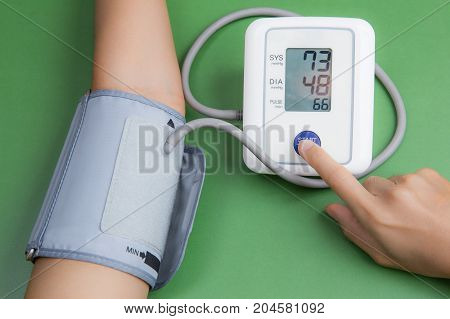measuring blood pressure with digital equipment on green background