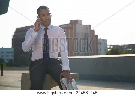 Serious young office worker wearing white shirt and tie, sitting outside, talking on mobile phone. Confident businessman having conversation in street. Business lifestyle concept