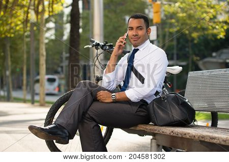 Handsome Hispanic businessman sitting on bench in park, talking on mobile phone, bike nearby. Smiling young office worker using smartphone. Modern technology concept