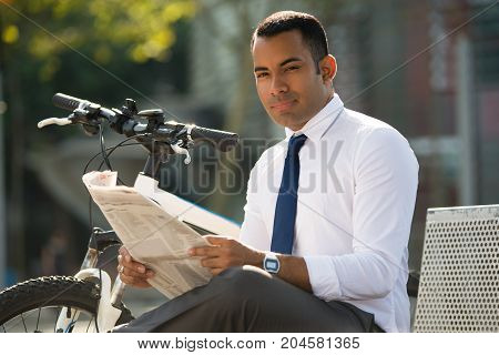 Young Latin businessman sitting on bench, holding newspaper, smiling at camera, bike nearby. Male office worker reading newspaper in park during lunchtime