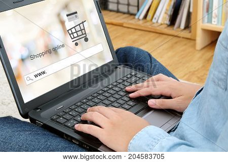 Hand tying laptop computer with www. on search bar over blur store background on screen on line shopping business and technology E-commerce digital marketing concept