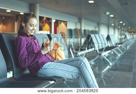 Girl at the airport window sits on the banch and looking at smartphone