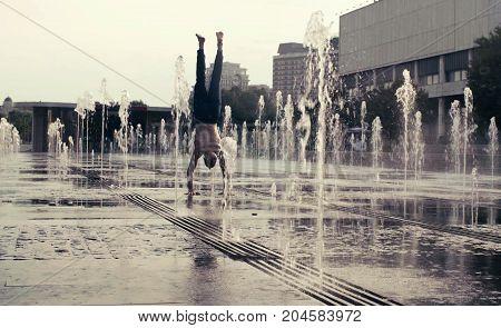 Strong man performing handstand in the fountain. Yoga asana - adho mukha vrksasana