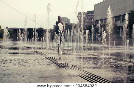 Strong man performing one-leg standing balance in the fountain. Yoga asana - utthita hasta padagushthasana