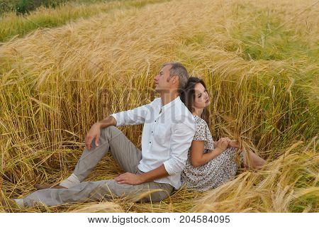 Unappy Love Couple Sitting On The Grass In A Wheat Field. Man And Woman Quarreled.