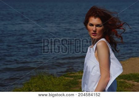 Serious Girl In White Dress With A Stern Gaze Outdoors On River Shore, Deep Blue Water On Background