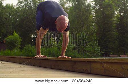 A man doing yoga exercises in the park. Urdhva mukha svanasana, Artha mukha svanasana. Bakasana