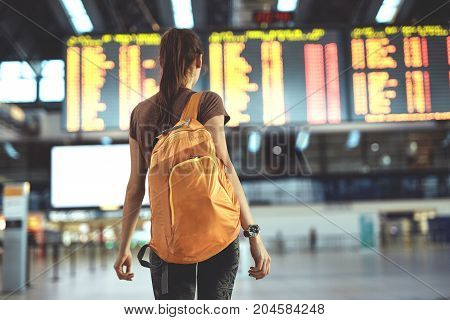 Young woman with small backpack as a hand luggage in international airport looking at the flight information board, checking her flight