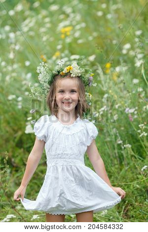 Little Girl With Wreath From Flowers On The Head