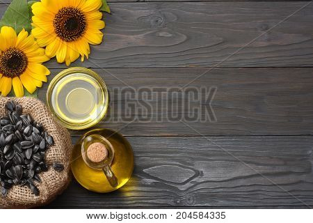 Sunflower Oil, Seeds And Flower On Dark Wooden Background. Top View With Copy Space