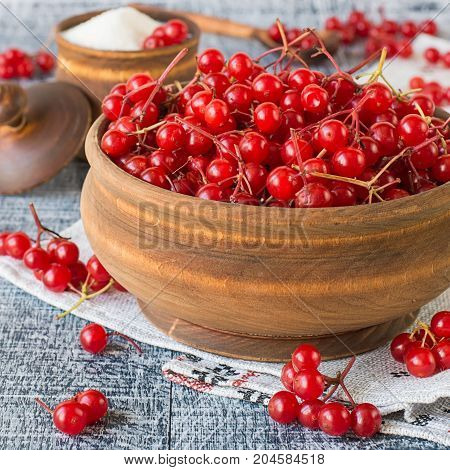 Ripe red berries of a viburnum in a round wooden bowl on an embroidered napkin on an old wooden table. The source of natural vitamins. Used in folk medicine. Selective focus.