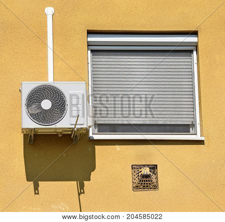 Air conditioner on the wall next to a window