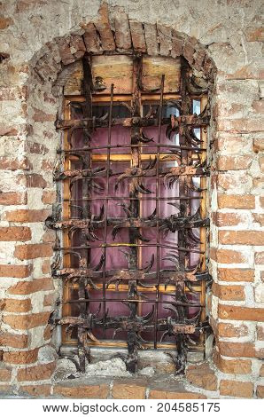 An old window with iron grating isolated on aged brick wall. Safety. Security.